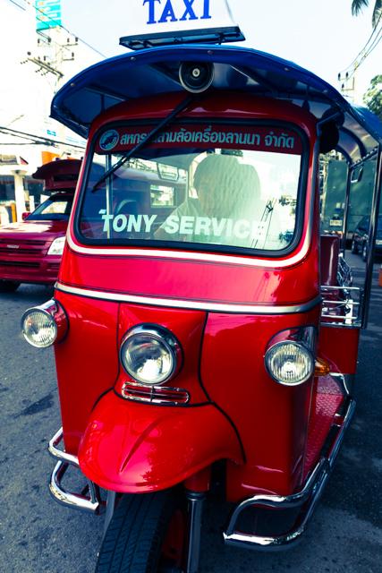 赤いトゥクトゥクの運転席に座り記念撮影